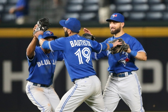 Toronto Blue Jays outfielders, from left, Ben Revere, Jose Bautista and Kevin Pillar celebrate after the Blue Jays defeated the Atlanta Braves 5-0 in a baseball game Thursday, Sept. 17, 2015, in Atlanta. (AP Photo/John Bazemore)