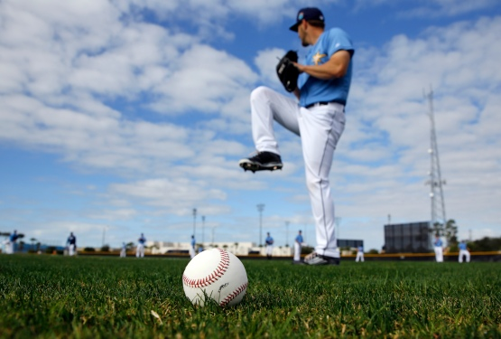 A baseball sits on a field as Tampa Bay Rays pitcher Adam Wilk warms up during a spring training baseball workout in Port Charlotte, Fla., Sunday, Feb. 21, 2016. (AP Photo/Patrick Semansky)