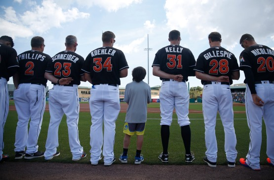 Miami Marlins' fan Joey Silverstein, stands with the team during the national anthem, before an exhibition spring training baseball game against the New York Mets, Thursday, March 17, 2016, in Jupiter, Fla. (AP Photo/Brynn Anderson)