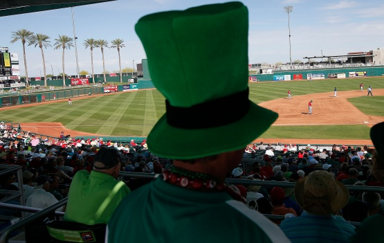 A Cincinnati Reds fan dons his St. Patrick's Day hat as he watches the sixth inning of a spring training baseball game against the Cleveland Indians Tuesday, March 17, 2015, in Goodyear, Ariz. (AP Photo/Ross D. Franklin)